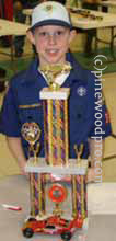 pinewood derby winner with car and trophy