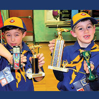 Pinewood Derby winners with their cars and trophies