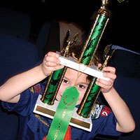 cub scout looking at trophy