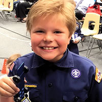 excited cub scout with pinewood derby car